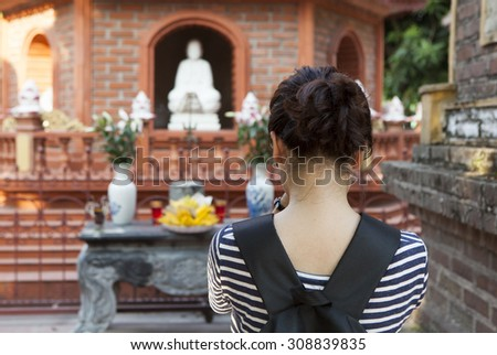 Young Vietnamese girl comes to Tran Quoc pagoda to pray for peace and happiness. This is the oldest Buddhist temple in Hanoi, Vietnam. - stock photo