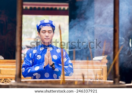 Young Vietnamese man praying in front of urn with incense sticks - stock photo