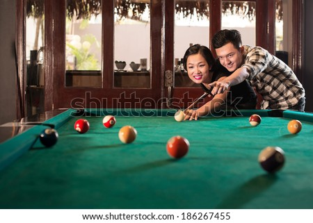 Young Vietnamese man teaching his girlfriend to play pool - stock photo
