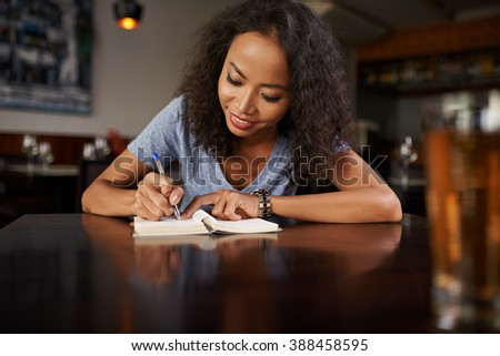 Young Vietnamese woman writing down her ideas - stock photo