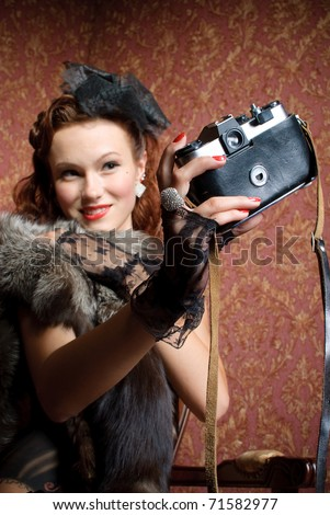 young vintage woman with camera in old-style studio
