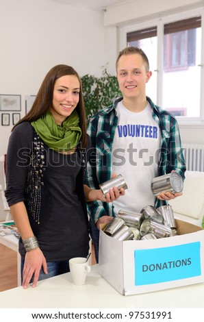 young volunteer couple  doing community service with donation box - stock photo
