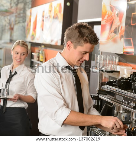 Young waiter and waitress working in bar serving coffee - stock photo