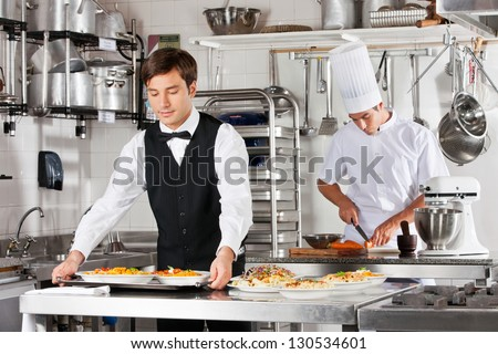 Young waiter carrying tray of dishes with chef working in commercial kitchen