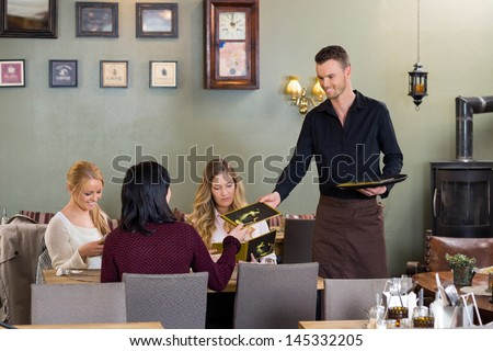 Young waiter giving menu to female customers at restaurant - stock photo