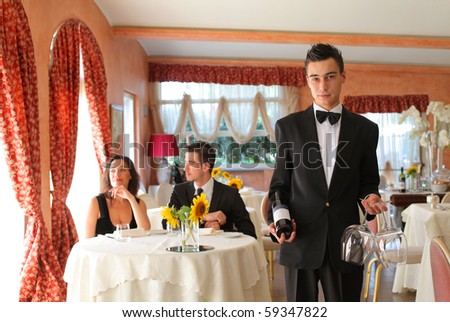 Young waiter in a restaurant with couple on the background - stock photo