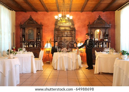 Young waiter serving some wine to a newly married couple - stock photo