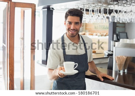 Young waiter smiling and holding cup of coffee at the cafe - stock photo