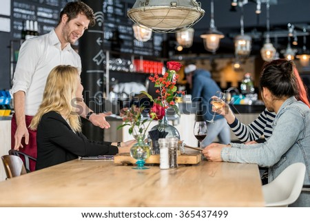 Young waiter taking order from customers at table in cafe