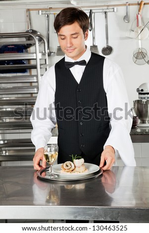 Young waiter with salmon roll and white wine in commercial kitchen
