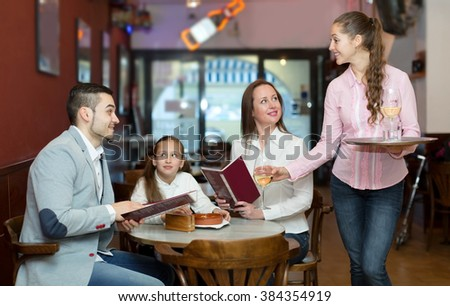 Young waitress and cheerful family with daughter reading menu. Focus on the waitress