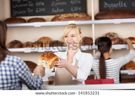 Young waitress giving bread loaf to customer with coworker working in background at cafe