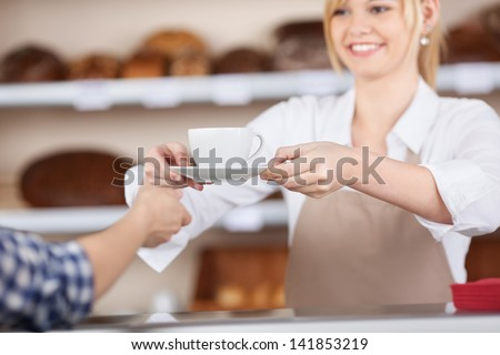 Young waitress giving coffee cup to customer in cafe - stock photo