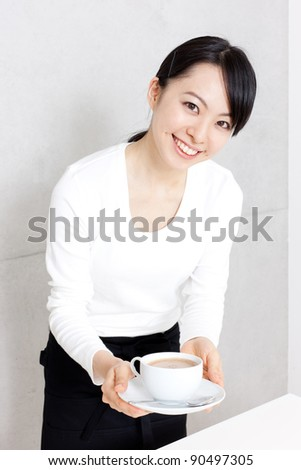 young waitress serving coffee isolated on white background - stock photo