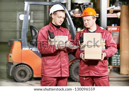 young warehouse workers in uniform in front of forklift stacker loader - stock photo