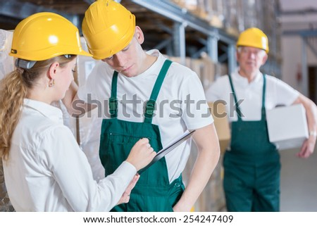 Young warehouseman having conversation with young female boss - stock photo