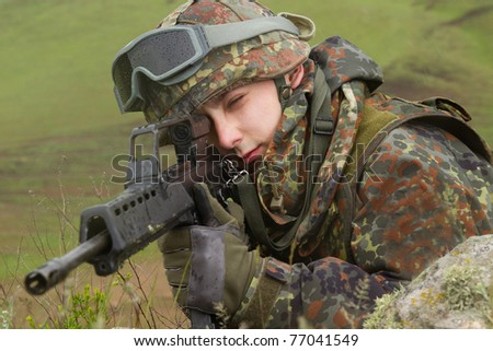 Young warrior hiding behind the rock with a gun