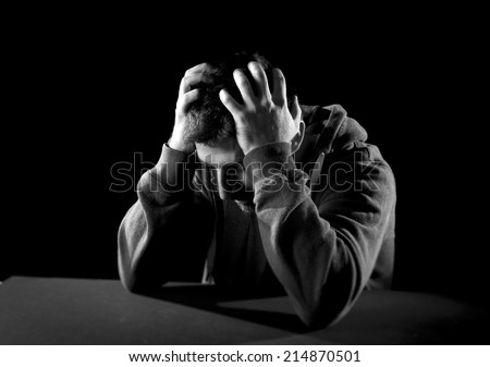 young wasted man with hands covering face suffering deep depression, pain, emotional disorder, grief and desperation concept isolated on black background with grunge studio lighting in black and white - stock photo