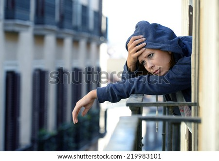young wasted woman in hood suffering depression and stress outdoors at the balcony window in pain and grief feeling sad and desperate in urban background - stock photo