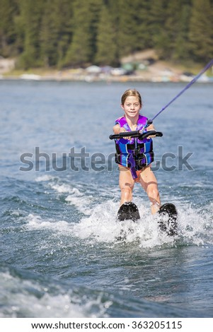 Young Waterskier on a beautiful scenic lake  - stock photo