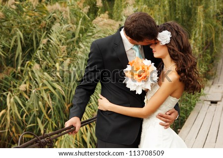 young wedding couple, beautiful bride with groom portrait on the bridge, summer nature outdoor - stock photo
