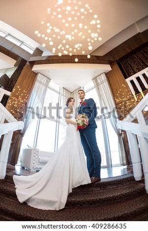 Young wedding couple enjoying romantic moments indoors against window. Beautiful modern interior. Fisheye lens  - stock photo