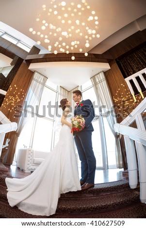 Young wedding couple enjoying romantic moments indoors on stairs against window. Beautiful modern interior. Fisheye lens  - stock photo