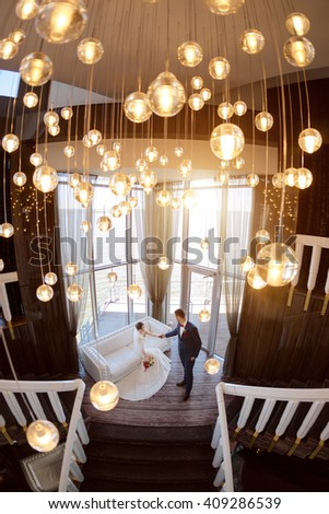 Young wedding couple enjoying romantic moments indoors sitting on sofa against window. Beautiful modern interior - stock photo