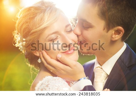 Young wedding couple enjoying romantic moments outside on a summer meadow - stock photo