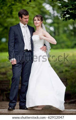 young wedding couple - freshly wed groom and bride posing outdoors on  their wedding day