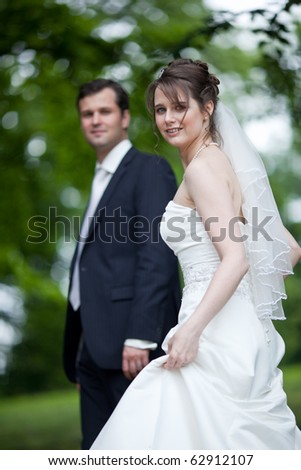 young wedding couple - freshly wed groom and bride posing outdoors on  their wedding day - stock photo