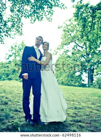 young wedding couple - freshly wed groom and bride posing outdoors on  their wedding day (color toned image) - stock photo