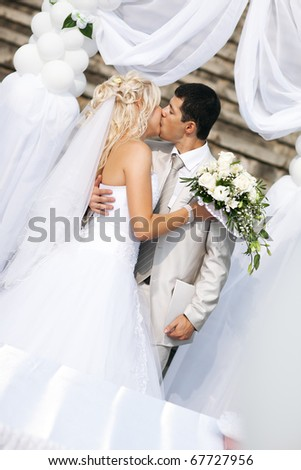 Young wedding couple kissing. White colors. - stock photo