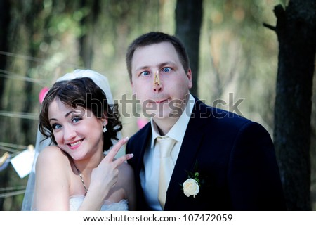 Young wedding couple outdoors funny portrait with a clothespin on their nose - stock photo