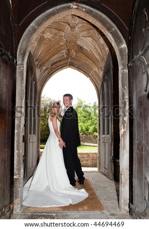 Young wedding couple posing in an English medieval church entrance