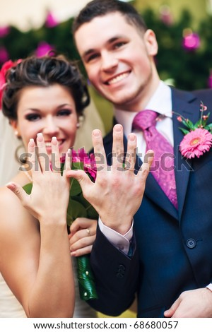 Young wedding couple showing their rings. Focus on hands. - stock photo