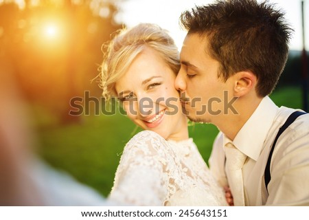 Young wedding couple taking a selfie of themselves as they enjoy romantic moments outside on a summer meadow - stock photo