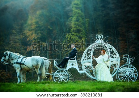 Young wedding romantic couple of bride in white dress and bridegroom in suit in cinderella carriage with horses in deep green forest outdoor on natural background, horizontal picture - stock photo