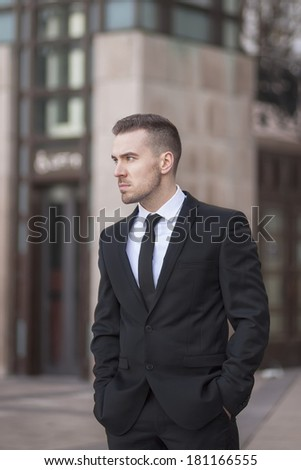 young well-dressed businessman standing outdoors