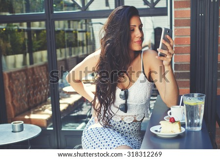 Young well dressed woman with a perfect figure looking to her smart phone screen while breakfast in restaurant terrace,attractive latin female browsing internet on her touchscreen phone at coffee shop - stock photo