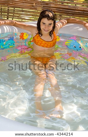 Young wet girl child swimming in swimming-pool - stock photo