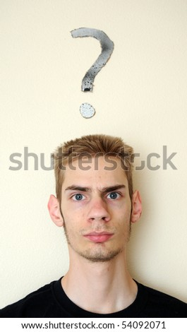 Young white Caucasian male adult staring forward, confused, with a question mark above his head on the wall behind him. Focus point is on the person.