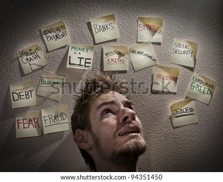 Young white Caucasian male is overwhelmed with stress and worry about the bad economy crises during this economic recession or depression. - stock photo