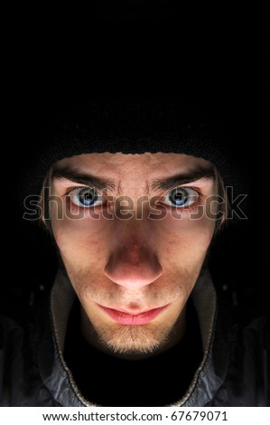 Young white Caucasian male wears a black beanie surrounded by a black copyspace background. - stock photo