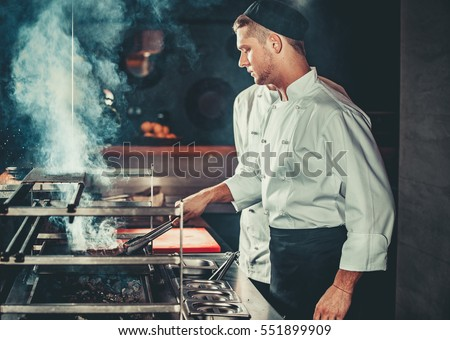 Young white chef in black apron and hat standing near the brazier whith coals. Man cooking beef steak in the interior of modern professional kitchen