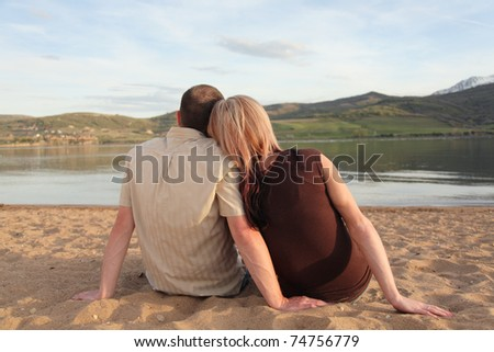 young white couple sitting on beach at mountain lake from behind