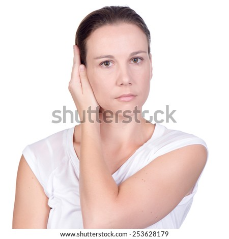 Young white deaf or hearing impaired woman holding her hand or both hands over her ears to shut out noise on white background in studio - stock photo