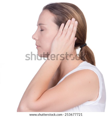 Young white deaf or hearing impaired woman holding her hand or both hands over her ears to shut out noise on white background in studio; facing away from the camera with eyes closed - stock photo