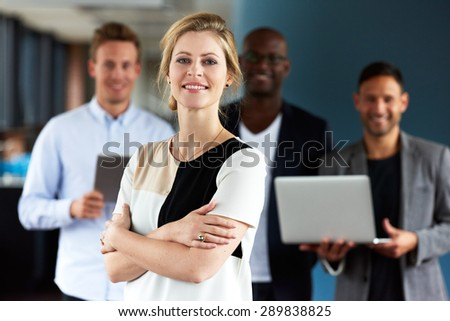 Young white female executive facing camera with arms crossed with colleagues in background - stock photo