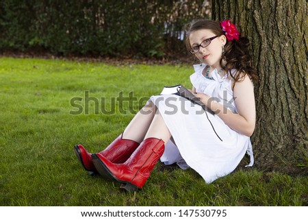 Young white girl in red boots looking up at camera sitting under tree reading - stock photo
